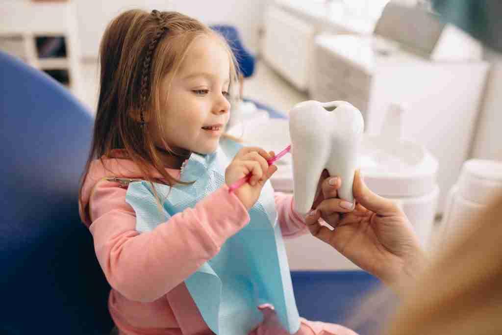 Menina escovando o objeto em forma de dente